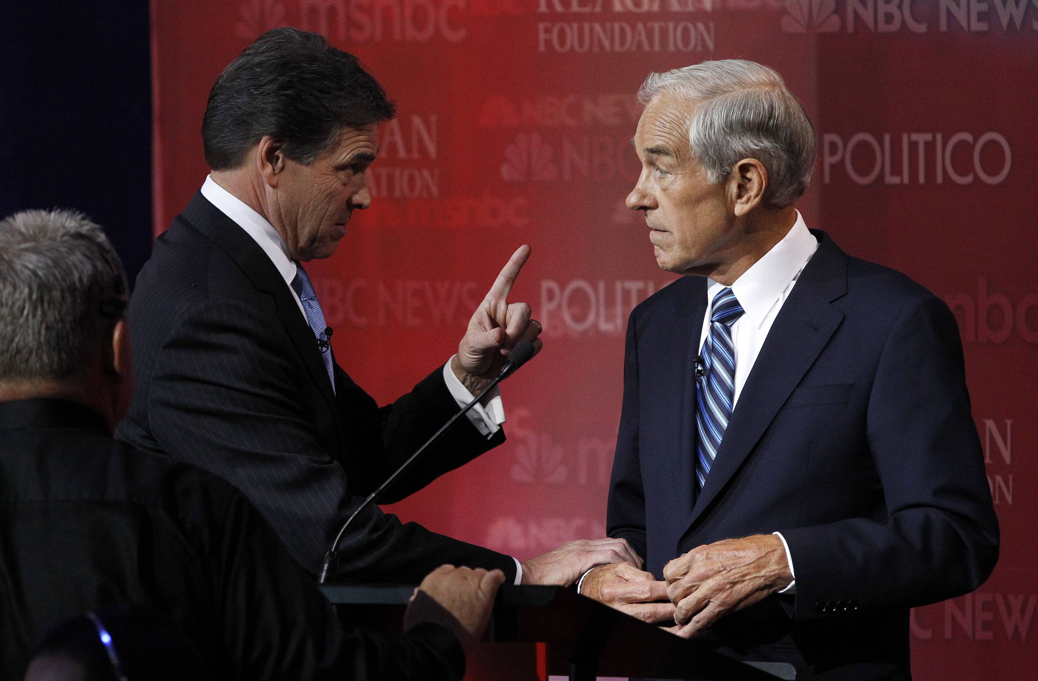 Texas Governor Perry talks during a break with Rep. Ron Paul on stage ...